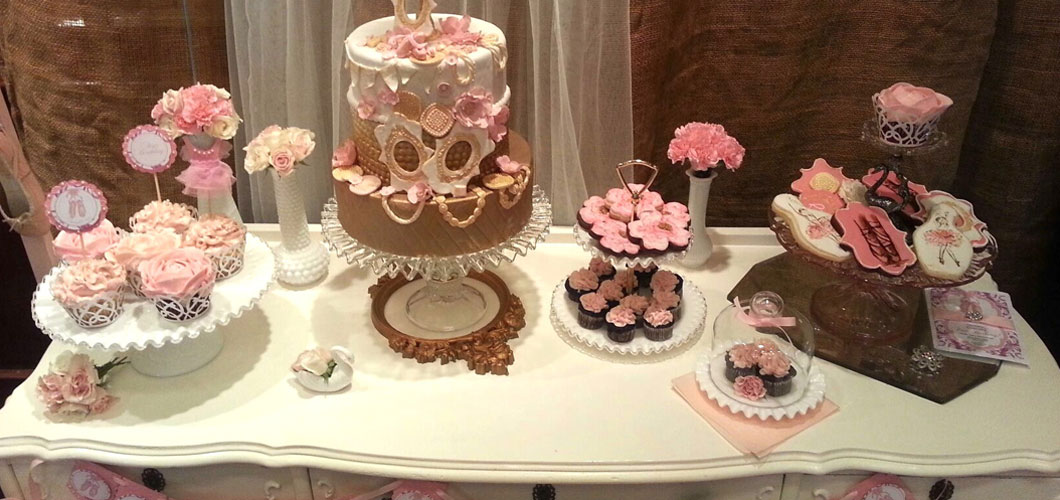 antique dessert table with decorative cake, cupcakes, flowers